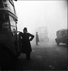 Ernst Haas  A policeman leans against the bonnet of a bus talking to the driver on a foggy day in London 1955