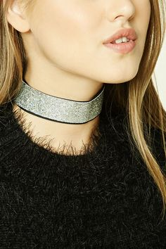 A thick textured choker featuring a glitter design, a velvet lining, high-polish ends, and a lobster clasp closure.
