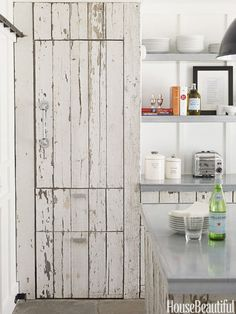 Designer Ken Fulk combined fresh white paint and battered wood in a weekend house that manages to be both striking and relaxed. The cabinetry and paneling are made from old fencing and the handles are actually galvanized pipe. Click through for more kitchen cabinet design ideas.