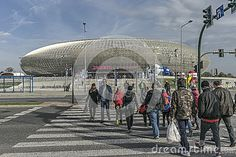 Tauron Arena in Cracow. Modern entertainment and sports venue. The biggest one in Poland. And people going to the Hall by the pedestrian crossing