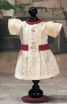 """J'aime Ma Bleuette : 24 Au Concert Lot Number:  24 the dress appeared as costume #1 in the Winter 1938/1939 catalog described as """"robe blanche de soierie brochee"""",with red velvet sash and collar,and decorative buttons Realized Price:  $1,500"""