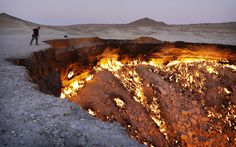 """A tourist peers into the Darvaza Gates Of Hell gas crater in the Karakum Desert, Turkmenistan. The eerie cavern has been on fire for more than 40 years. [File this under: """"Don't Go"""" o_O]"""