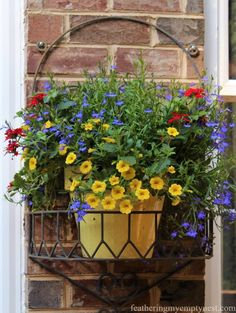Vibrant pots of yellow Million Bells, red Verbena, and blue Lobelia provide splashes of summer color to the brick wall ---Summer Flower Planters On The Deck
