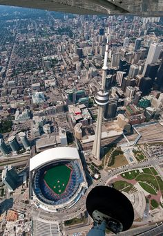 cn tower as it stands next to rogers centre, home of the blue jays; toronto, ontario, canada