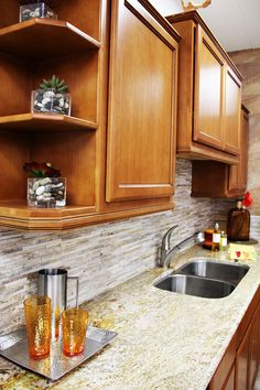 Shown: Custom Cabinetry, Stone Panelling, Granite Counter And Stainless  Steel Sink. What