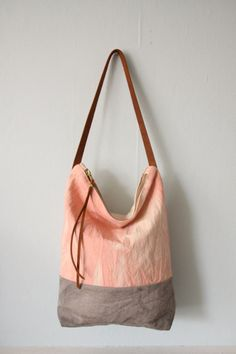This tote bag features a cotton canvas exterior hand dyed with natural Madder and Pomegranate dye. The bag is fully lined with hand screen printed cotton and has an inner pocket. The tote is finished off with a durable metal zipper, sturdy leather strap and leather zipper pull.