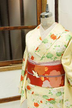 霰のような地文様浮かぶクリーム色の地に、椿を思わせる紅白の花枝が染め出された綸子袷着物です。