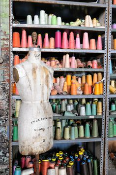 Antique mannequin dress form and shelves full of colorful thread on bobbins in an abandoned sewing factory from bygone industrial America.