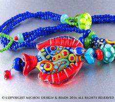 Eine glückliche Halskette in leuchtenden Farben. Hergestellt aus meinem Lampwork Glasperlen, handgefertigte Glasperlen Button und Samen. Zwei Stränge der königsblauen TOHO Glas Rocailles bilden die Halskette. Die Fass geformte Perle liegt direkt in der Mitte, darunter eine Benzin-Perle mit Türkis Punkten und eine rote kleine Spacer Perle. Mit dieser Kette ist ein glücklich roter Fisch.  Es ist auf Super-starke Softflex-aufgereiht und der Headpin ist Sterling Silber.  Es ist 19(48 cm) lang…