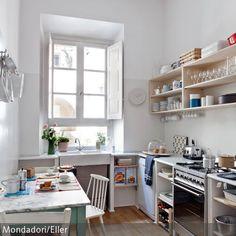 Die Küche ist in sanften Farben gehalten. Stühle, Fensterläden und Wände in strahlendem Weiß, ein Regal aus hellem Holz und ein Esstisch mit grünen Beinen…