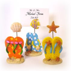 These adorable beach flip flop placecard holders are the perfect way to display your wedding place cards. They will also make a perfect favor for your guests to display their vacation photos once they get home. Each place card holder is made of poly resin and comes in 3 assorted colors and designs. Blue flip flop with fish, yellow with star fish and red with shell.  #weddingfavor #flipflop #placecard #summer #beach
