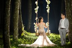Bride's pre-wedding session on a swing entwined with romantic white florals // Gerry and Devina's Engagement With a Giant Floral Wreath at Pine Forest, Bandung