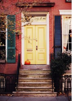Never would have thought a bright yellow door would work on a brick house with dark green shutters...and then I see this...