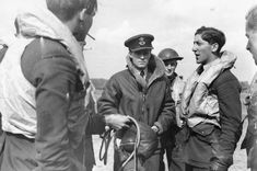 """P/O Stanley CN """"Stan"""" Norris (second right) recounts at RAF Hawkinge how he claimed a Do 17 damaged on 29 July 1940. The day recorded in the ORB of No 610 Squadron RAF a scramble to help meet a force of 48 Ju 87 dive bombers accompanied by 80 Me 109 fighters but arriving too late. On return, the 21-year-old pilot was unhurt in Spitfire Mk I DW-O after suffering a burst tyre before ground-looping on landing."""