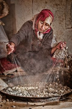 Silk filaments being unraveled from silk Cocoon. by Davie Gan A Uyghur lady processing her batch of Silk Worm Cocoon for their precious cargo of silk threads. Xinjiang Uyghur Autonomous Region, China