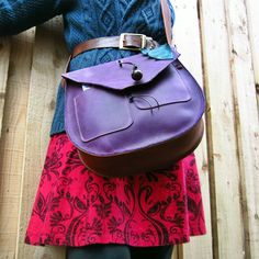 Very much a satchel feel to this big beauty! Made using rich VIOLET, CONKER leather. Unique Rag tag raw edge with Dragonfly leaf detailing. Features 2 Large front pockets for ipods, mobile, purse, etc! Fairysteps egg bead wooden closure. Very large, deep main compartment with an unlined, smooth, clean interior. Stitched, wide comfortable strap. Complete with matching leafy keyfob to stop the pixies stealing your keys..