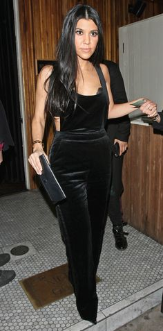 Kourtney Kardashian in black velvet overalls
