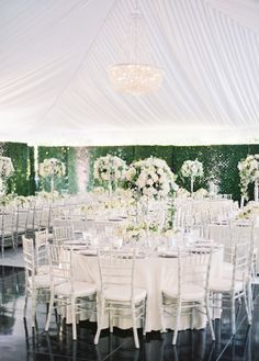 light and airy elegant tented wedding reception   white on white on white   tall centrepieces   Black Tie Secret Garden Wedding