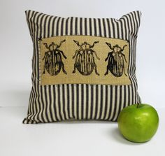 Block Print Beetle Insect Pillow. Decorative throw pillow cushion cover with Bug block print print in black ink The front of the pillow is constructed out of a black and ivory cotton ticking with the stripes running horizontally. At the center there is a burlap piece of burlap with three beetle bug insect hand block printed printed with black fabric ink the burlap piece is applied using a reverse applique method. The back is fabricated with taupe cotton with a black exposed zipper for…