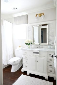 DIY Beautiful Spa Like Bathroom Makeover - Lowe's allen + roth Vanover white undermount vanity with marble top, Home Depot Calacatta Gold polished marble mosaic tile above sink, The Bath Company Newport Brass faucet (love the hot/cold signage button switch out!), Target Threshold Chunky bath rug, Pottery Barn Ruffle shower curtain, Schoolhouse Electric Montclair Double Sconce & HP-2274-04-2.25SH striped glass shades, walls are Benjamin Moore Pale Oak