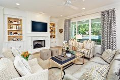 A neutral color palette allows for a fun and playful mix of patterns in this transitional living room. Further visual interest comes from the built-in shelves framing the fireplace: the interior is painted a warm neutral to complement the space.