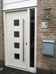 Voordeur paneel in kunststof kozijn van HBI. Adeco type Dicoma deurpaneel met lange RVS greep deuroverlappend, en helder glas.