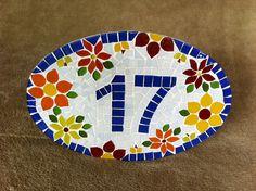 Placa com número residencial para áreas externas feita em base de cerâmica. Trabalho em mosaico com pastilhas de vidro , pastilhas cerâmicas e azulejos especiais. Acompanha argamassa para ser assentada em muros, paredes ou pode ser feita com furos para ser afixada com parafusos.  Pode ser feita t...