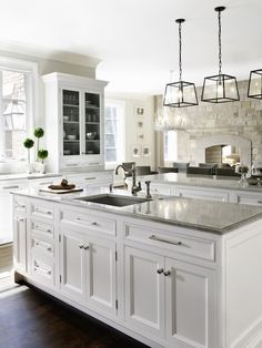 Love the countertops, the non white sink against the white cabinets, and the hanging fixtures.