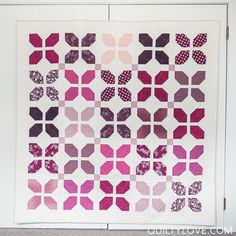 VandCo Simply Colorful flower petal quilt in Purple. Quilt made with A moda layer cake and white sashing.