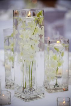 I like the flowers glass vases filled with water, topped with a floating candle!  Trish?
