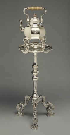 "Antique Silver Tea Kettle with Stand. The ""Queen Anne"" style kettle (1724-1725), with its stand and spirit burner and its accompanying silver table, is the most important surviving work  of the celebrated Huguenot silversmith Simon Pantin, who was active in London in the first three decades of the eighteenth century. Pantin enjoyed the patronage of influential fashionable clients, including the king. The owners of this piece of tea equipment, George Bowes and his wife Eleanor Verney."