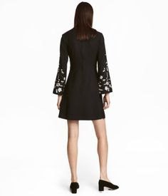 Black. Short dress in woven, crêped fabric with a V-neck at front and concealed zip at back. Seam at waist and long, flared sleeves with embroidery and