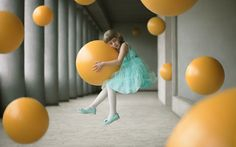 """Open, Enhanced Far from gravity (Lontano dalla gravità) «Una bambina in assenza di gravità tiene in mano una sfera in mezzo ad altre sfere uguali. La bambina rappresenta la dolcezza e la fragilità. Associata con la sfera, che esprime la leggerezza, è simbolo della parola """"innocenza"""". In questa immagine, il tempo sarebbe sinonimo di gravità. La foto è stata scatta a Grenoble, Francia, il 9 aprile 2016». (© Alex Andriesi, Romania, Shortlist, Open, Enhanced, 2017 Sony World Photography Awards)"""