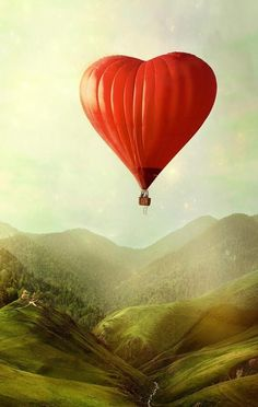Red heart shaped hot air balloon above a green valley.
