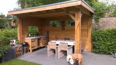 Eiken overkapping met steigerhouten meubels en eiken buitenkeuken