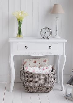 Basket with cushions/throws under hall table.