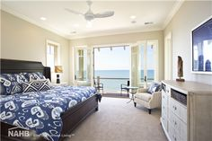 A master bedroom with glass windows and doors that open to an impressive beach view. It also has a dark wooden bed that faces the chest drawer and accent chair. Wood Bedroom Sets, Window Seat Nook, Cottage Style Furniture, Master Bedroom Accents, Blue Master Bedroom, Built In Bookcase, Gray Bedroom Walls, Bulkhead Bedroom, Beach Style Bedroom