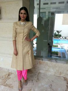 Esha Gupta wearing a pink dhoti and cream kurta with statement necklace. Indian fashion. Bollywood fashion.