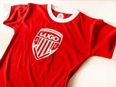 La camsiseta T-Shirt brook Blanca/Roja de niños es una camiseta roja toda ella, con contraste en blanco en el cuello y en las mangas, 100% algodón, peinado en canalé e 1x1 con elastán.    Esta camsieta es serigrafiada en color blanco con el escudo del Club Deportivo Lugopor la parte delantera, en la parte de la nuca tiene el mismo escudo en blanco pero en un tamaño más pequeño.