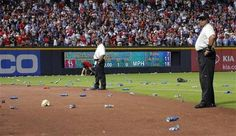Guards stand by while Atlanta fans throw a variety of items, from beer bottles to wrappers, after a questionable infield fly rule call.