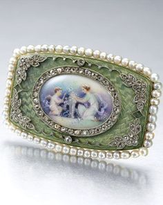 GEM-SET AND DIAMOND BROOCH, CIRCA 1910 The tonneau shaped plaque, centring on a painted ivory miniature of Venus and Cupid, to a background applied with light green guilloché enamel, embellished with rose-cut diamonds and set within a border of seed pearls, French assay marks.