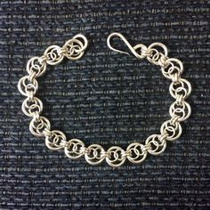 This beautiful and stunning bracelet is a Chainmail Infinity Link Style. This bracelet is made of 14, 16, and 19 gauge 935 Argentium Sterling Silver. The bracelet is 9 1/4 inches or 21 cm long, 7/16 inches or 10 mm wide. It will fit a 7 1/4 - 7 3/4 inch wrist. Rings are cut with a saw for perfect closure, heat treated, and then tumbled for 8-12 hours. Contact me if you prefer a different length or a magnetic clasp in the last photo. This stunning bracelet is 100% hand fabr...