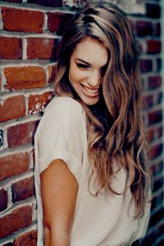 Picture of a senior girl leaning in a brick wall. Image by: pinterest.com
