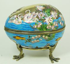 RUSSIAN__ silver enameled egg box depicting swans, flowers and fish. Gold wash throughout. Includes fitted stand with three figural eagle feet. Holds Cyrillic Pavel Akimov Ovchinnikov workmaster marks, 84 silver purity and town marks with Double headed eagle mark.