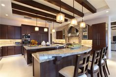Here's a second angle of the prior kitchen, revealing the rich, dark tone of the cabinetry and island wood, plus large steel range with patterned tile surround.