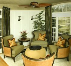 a cozy grouping of olive drab arm chairs. The addition of warm gold on the chair backs, throw pillows and ottoman, which looks like a yellow olive, provides some brightness and keeps the room from looking dull.
