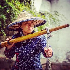 """A gondolier in Zhouzhuang (周庄) in Jiangsu Province China. This ancient village is one of several called """"Venice of the East."""" Though many tourists flock here it is with good reason. The village is located in a stunning natural setting and it has a rich cultural heritage."""