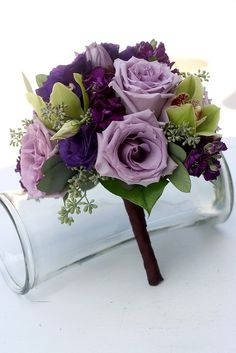 brides maid bouquet made with roses, orchids, lissianthus and stock
