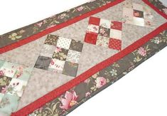 Add a touch of elegance to your buffet table, dining room table, sideboard, or dresser, with this quilted table runner made with florals, polka dots, and tonal patterns for a sophisticated result. The four patchwork blocks feature coordinating prints in aqua, gray, rosey red, and