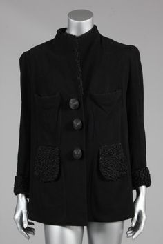 * Elsa Schiaparelli couture black wool and astrakhan jacket, circa 1939-1940, with printed petersham label 'Schiaparelli London', the loose jacket with three massive coiled leather buttons, copper-hook fastenings concealed behind the closure flap, with unusual hour-glass shaped front panels forming deep chest pockets lined in fur, curved pocket flaps at the waist over diagonal vents, astrakhan trim also to the lapels (which can be worn open or closed), and cuffs, slight padding to the…